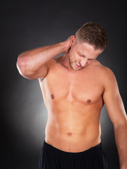 Fit muscular man massaging his neck in pain