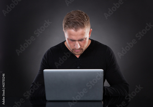 Man or hacker working on a laptop at night