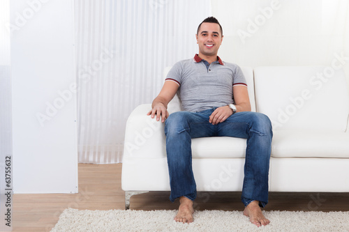 Happy Young Man Sitting On Sofa
