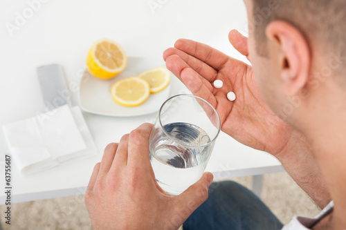Sick Man Taking Tablets With Glass Of Water