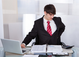 Businessman Suffering From Backache At Desk