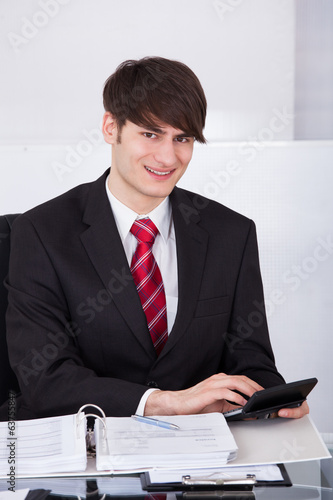 Businessman Calculating Finance Using Calculator At Desk