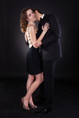 Young Couple Embracing Over Black Background