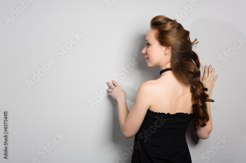 Woman standing face to the wall