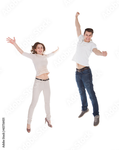 Couple In Casuals Jumping Over White Background