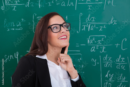 Thoughtful Teacher Looking At Chalkboard