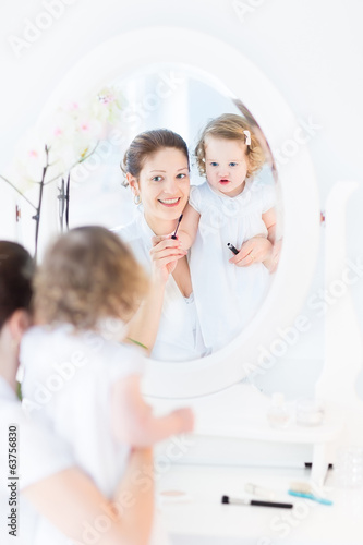 Young woman and her funny toddler daughter applying make up