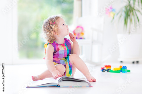 Funny curly toddler girl reading a book sitting on the floor