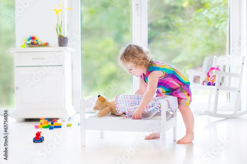Sweet curly toddler girl playing with her teddy bear putting him