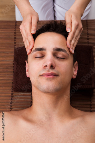 Man Receiving Head Massage From Massager In Spa