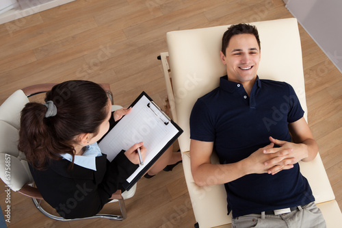 Male Patient Communicating While Psychologist Writing Notes