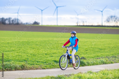 Happy young teenager boy riding his bike in european field