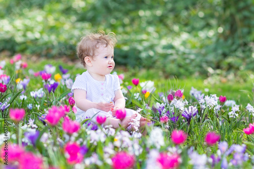 Cute smiling baby playing with first spring flowers