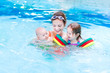 Young active mother having fun in a swimming pool with two kids