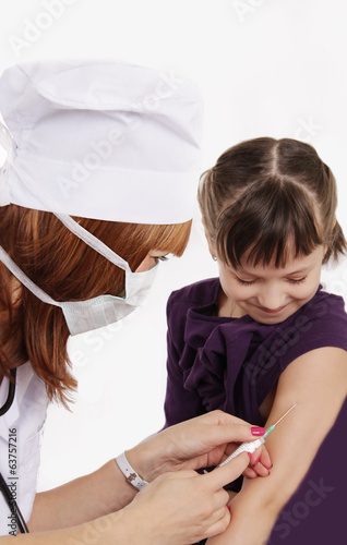 Woman doctor vaccinating girl in hand