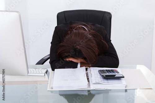 Businesswoman Tired Of Calculating Tax At Desk