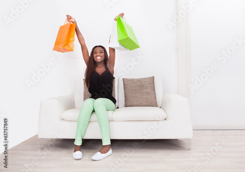 Woman Carrying Shopping Bags In Living Room