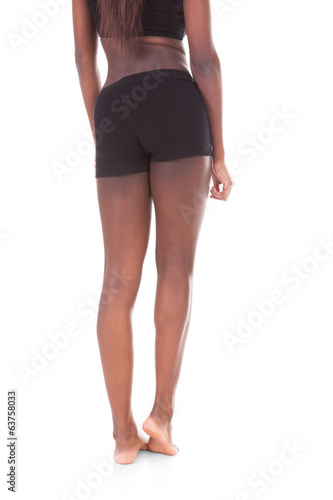 Low section rear view of young African American woman standing