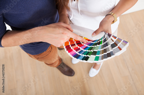 Couple Choosing Color For Wall At New Home