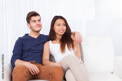 Smiling Young Couple Sitting On Sofa