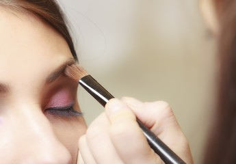 Makeup artist applying with brush cosmetic on eyebrow of woman