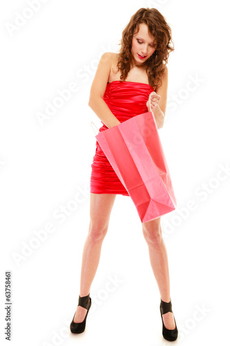 Full length of girl in red dress looking into shopping bag