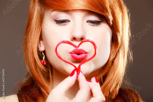 Redhaired girl holding heart love blowing kiss. Valentines day.