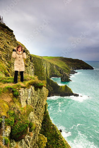 Woman standing on rock cliff by the ocean Co. Cork Ireland