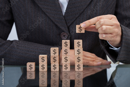 Businesswoman Stacking Dollar Blocks