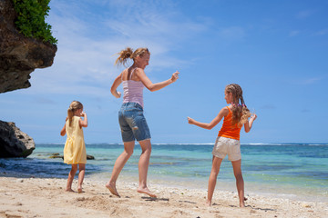 Happy family jumping at the beach in the day time