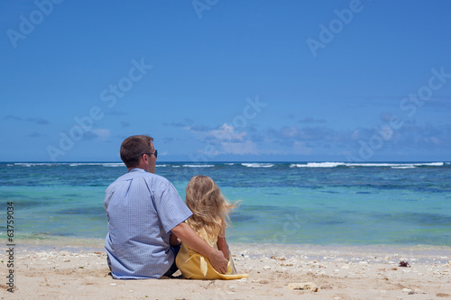 father and daughter sitting on the beach in the day time