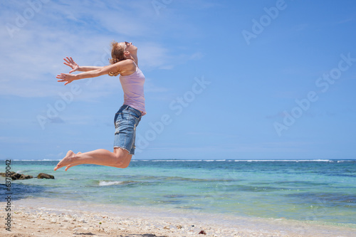 woman jumping at the beach in the day time