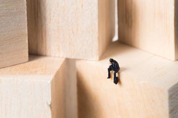 木のボックスの上で寂しく仕事をするビジネスマンのミニチュアの人形