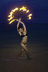 woman with fire on the beach at night