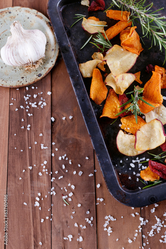Vegetable chips on a metal tray on a rustic wooden background