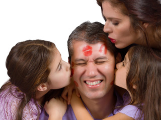Mother and daughters leave lipstick kisses on dad