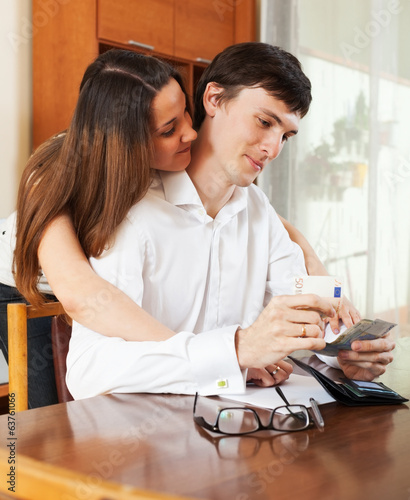 canvas print picture Man and woman calculating the budget