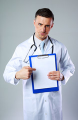 Dissatisfied male doctor showing on empty clipboard