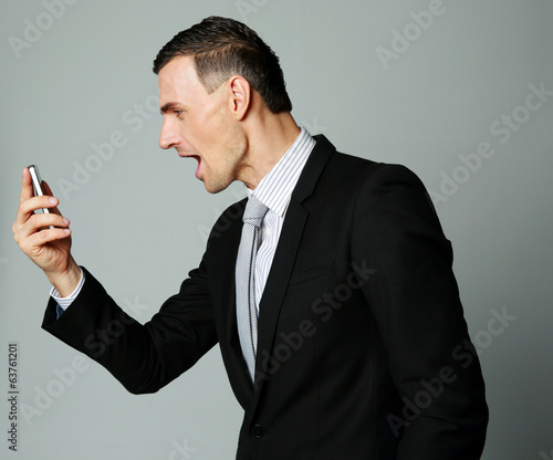 Angry businessman yelling on his cell phone on gray background