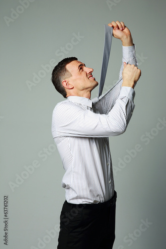 Businessman in suit hanging himself on tie