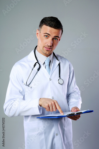 Male doctor telling diagnosis and showing on clipboard