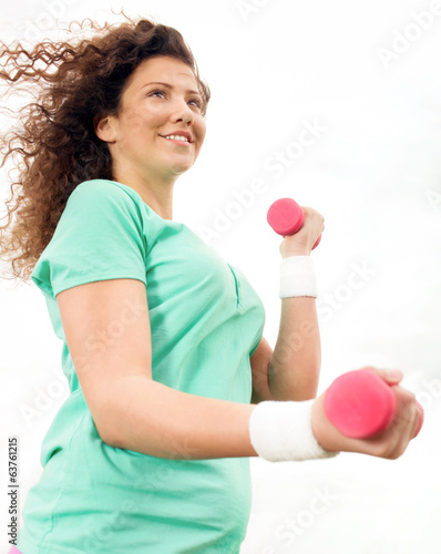 Happy Young Woman Practicing with dumbbell outside