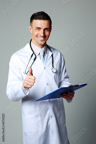Satisfied male doctor standing and giving thumb up