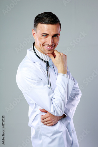Happy male doctor standing on gray background