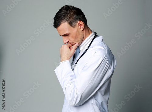 Portrait of a thoughtful male doctor on gray background