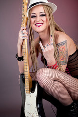 beautiful punk girl with lots of tattoos posing with guitar
