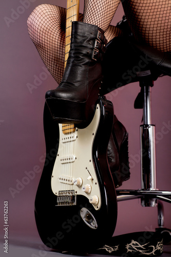 Funky young woman with her black hot guitar