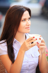 Woman drinking coffee and sitting outdoor
