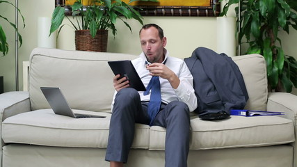 businessman with a tablet sitting on the sofa and eating a sandw