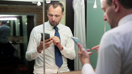 businessman using a mobilephone and looking at mirror